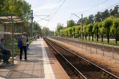 Jurmala, Letonia - 20 de mayo de 2017: Gente que espera el tren en la plataforma del ferrocarril Imagen de archivo libre de regalías