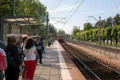 Jurmala, Letonia - 20 de mayo de 2017: Gente que espera el tren en la plataforma del ferrocarril Imagenes de archivo