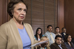 Juror In Jury Box. Juror stands in jury box holding paper during trial at courtroom stock image