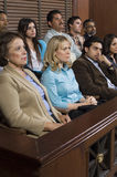 Jurors In Courtroom. Diverse group of jurors sitting in jury box of a courtroom during trial royalty free stock photos
