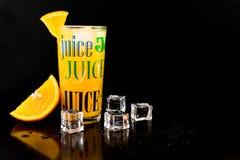 Jus d'orange dans un verre sur un fond noir photographie stock