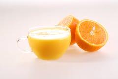 Jus d'orange dans une tasse transparente et des moitiés d'un ora mûr juteux Photographie stock