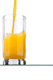 Jus d'orange dat in een lang glas wordt gegoten Stock Foto's