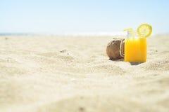 Jus d'orange in een kruik met kokosnoot op het strand Stock Foto's