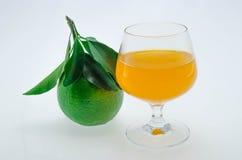 Jus d'orange en sinaasappelen met bladeren op witte achtergrond Stock Foto