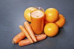 Jus d'orange et de carotte en verre avec du gingembre, légumes frais Photos stock
