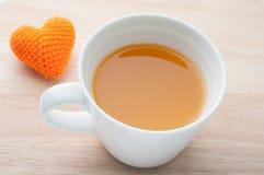 Jus d'orange et forme tricotée de coeur de tissus sur le backgroun en bois Photo stock