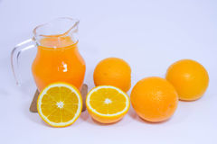 Jus d'orange et orange sur le fond blanc Photos stock