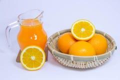 Jus d'orange et orange sur le fond blanc Image libre de droits