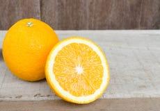 Jus d'orange et tranches d'orange placés sur une table en bois Photo stock