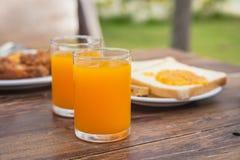 Jus d'orange frais avec le fond découpé en tranches de pain sur la table en bois Photographie stock