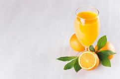 Jus d'orange frais dans le verre à vin avec de demi oranges mûres et feuille verte sur la table en bois blanche molle, vue supéri Image stock