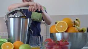 Jus d'orange frais fait maison de jeune garçon caucasien drôle dans la cuisine avec le presse-fruits électrique et le sourire banque de vidéos