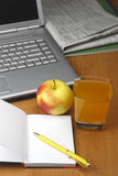 Jus d'orange, ordinateur portatif, pomme, bloc-notes et crayon lecteur Photo stock