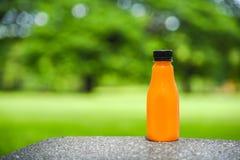 Jus d'orange in plastic fles op groene natuurlijke achtergrond Royalty-vrije Stock Foto's