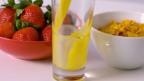 Jus d'orange versant dans le verre à la table de petit déjeuner clips vidéos