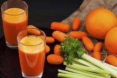 Jus de carotte avec le céleri et l'orange Images stock