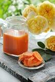 Jus de carotte dans un pot de verre transparent sur un fond des roses jaunes Image stock