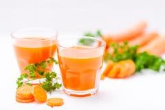 Jus de carotte en beaux verres, légumes oranges de coupe et persil vert sur le fond en bois blanc Orangeade fraîche U étroit images libres de droits