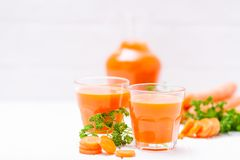 Jus de carotte en beaux verres, légumes oranges de coupe et persil vert sur le fond en bois blanc Orangeade fraîche U étroit photos libres de droits