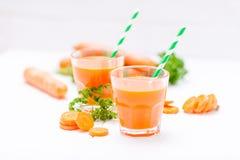 Jus de carotte en beaux verres, légumes oranges de coupe et persil vert sur le fond en bois blanc Orangeade fraîche U étroit images stock