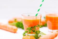 Jus de carotte en beaux verres, légumes oranges de coupe et persil vert sur le fond en bois blanc Orangeade fraîche U étroit image libre de droits
