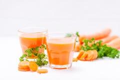 Jus de carotte en beaux verres, légumes oranges de coupe et persil vert sur le fond en bois blanc Orangeade fraîche U étroit image stock