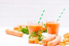 Jus de carotte en beaux verres, légumes oranges de coupe et persil vert sur le fond en bois blanc Orangeade fraîche U étroit photographie stock libre de droits