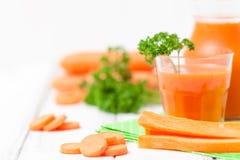 Jus de carotte en beaux verres, légumes oranges de coupe et persil vert sur le fond en bois blanc Orangeade fraîche U étroit photo stock