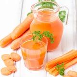 Jus de carotte en beaux verres, légumes oranges de coupe et persil vert sur le fond en bois blanc Orangeade fraîche U étroit photos stock