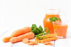 Jus de carotte en beaux verres, légumes oranges de coupe et persil vert sur le fond en bois blanc Orangeade fraîche U étroit photo libre de droits