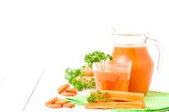 Jus de carotte en beaux verres, légumes oranges de coupe et persil vert sur le fond en bois blanc Orangeade fraîche U étroit photographie stock