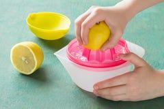 Jus de citron de compression avec le presse-fruits tenu dans la main photo stock