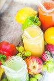 Jus de fruit fraîchement serré, fraise orange de raisin de kiwi de banane de smoothies de pomme vert-bleu jaune-orange de citron  Photos stock