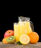 Jus de fruit frais en glace et parts sur le noir Image stock