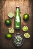 Jus de limette dans la bouteille avec les fruits de chaux et le presse-fruits frais de main sur le fond en bois rustique Images libres de droits