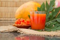 Jus de papaye frais dans le verre avec les fruits, la feuille et les tranches de papaye Photo stock
