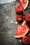 Jus de pastèque dans des bouteilles avec de la glace Photographie stock libre de droits