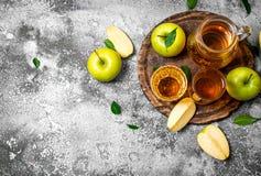 Jus de pomme dans le broc sur le conseil avec des pommes fraîches et vertes Photos stock