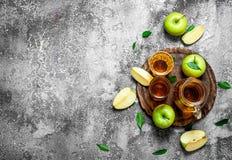 Jus de pomme dans le broc sur le conseil avec des pommes fraîches et vertes Images stock