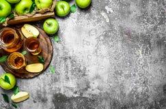 Jus de pomme dans le broc sur le conseil avec des pommes fraîches et vertes Image stock