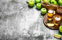 Jus de pomme dans le broc sur le conseil avec des pommes fraîches et vertes Photo libre de droits