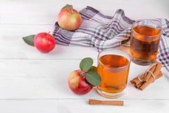 Jus de pomme dans un verre avec les pommes et la cannelle rouges mûres sur une table en bois blanche photographie stock libre de droits