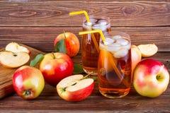 Jus de pomme organique frais de ferme avec de la glace en verre avec les pommes rouges entières et coupées en tranches crues Image libre de droits
