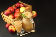 Jus de pomme pressé frais non filtré Jus et pommes de pomme sur la table en bois Un jus sain pour des athlètes Photographie stock libre de droits