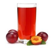 Jus de prune dans un verre avec le fruit frais de prune d'isolement sur le fond blanc Photos stock