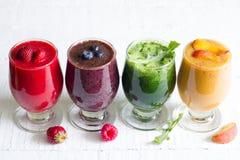 Jus de Smoothie avec les fruits et légumes crus frais sains sur les planches blanches Image libre de droits
