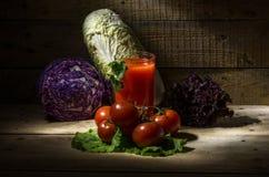Jus de tomates avec des tomates et des légumes Photos libres de droits