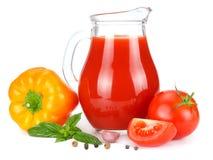 Jus de tomates dans la cruche en verre avec la tomate, l'ail, les épices, et le basilic d'isolement sur le fond blanc Photo stock
