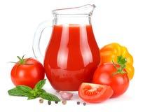 Jus de tomates dans la cruche en verre avec la tomate, l'ail, les épices, et le basilic d'isolement sur le fond blanc Photos stock